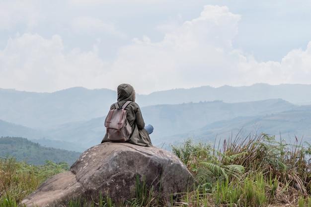 Chica inconformista sentada en rocosa de montaña