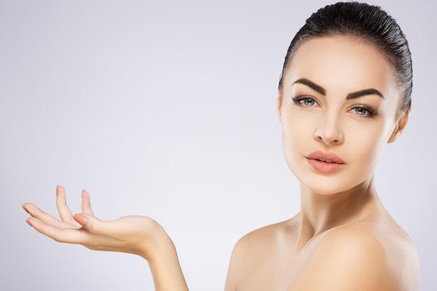 Chica increíble con cabello negro fijo detrás, ojos grandes, cejas gruesas y hombros desnudos sosteniendo la mano cerca de la cara en el fondo gris, espacio de copia, mostrando el producto.
