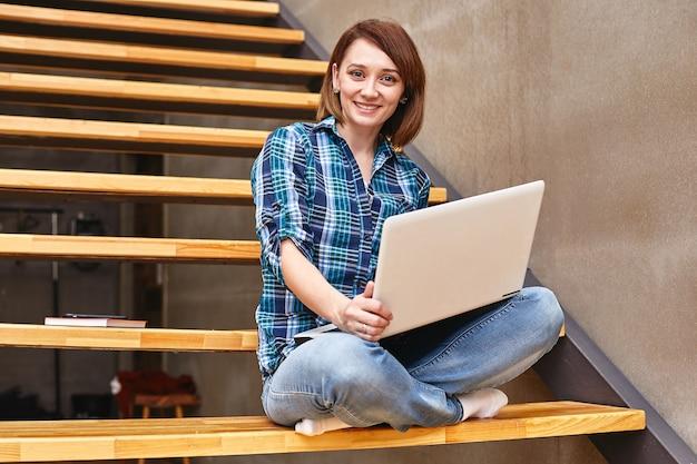 Chica independiente feliz trabajando en la computadora portátil en la casa
