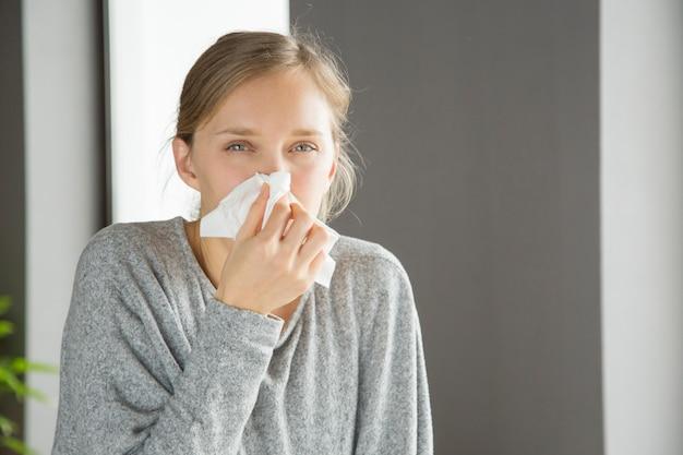 Chica infeliz pensativa que sufre de correr la nariz