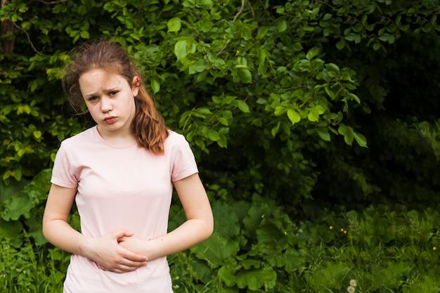 Chica inocente sosteniendo su estómago mientras tiene dolor de estómago en el parque