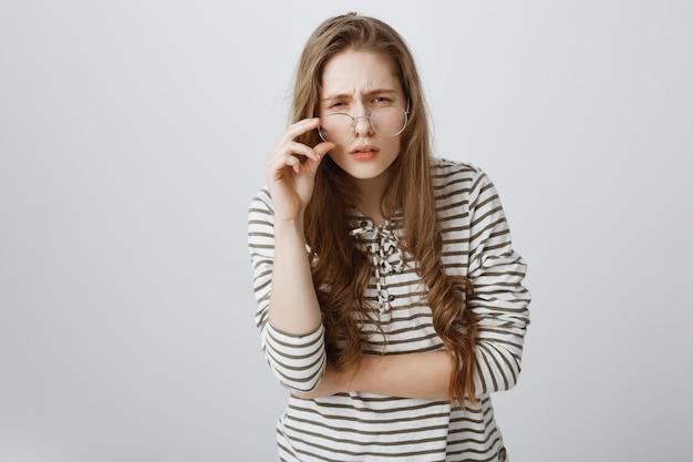 Chica insegura con mala visión, entrecerrar los ojos y mirar con gafas