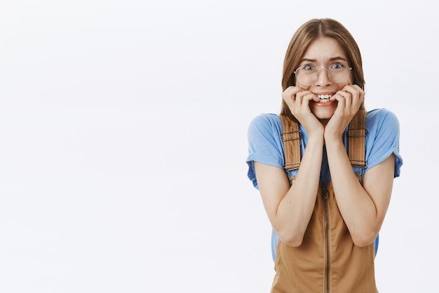 Chica insegura y preocupada mordiéndose las uñas y mirando horrorizada o asustada