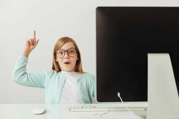 Chica inteligente bastante encantadora que usa su computadora para aprender cosas nuevas y contarlas