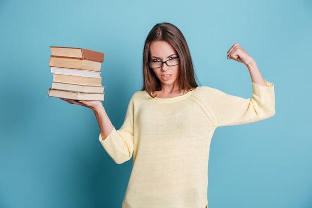 Chica inteligente fuerte sosteniendo libros en una mano usando anteojos aislados en el fondo azul