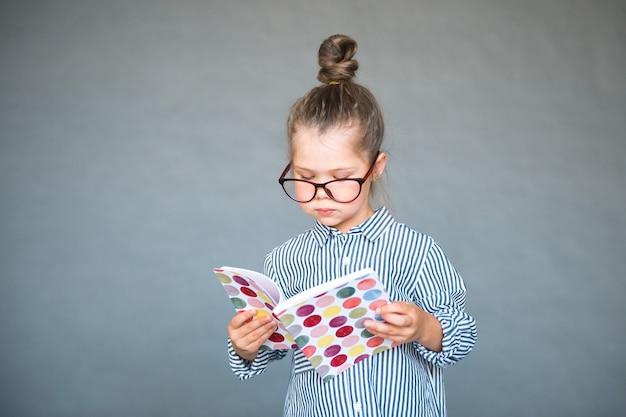 Chica inteligente en gafas leyendo libro de copia de regreso a la escuela