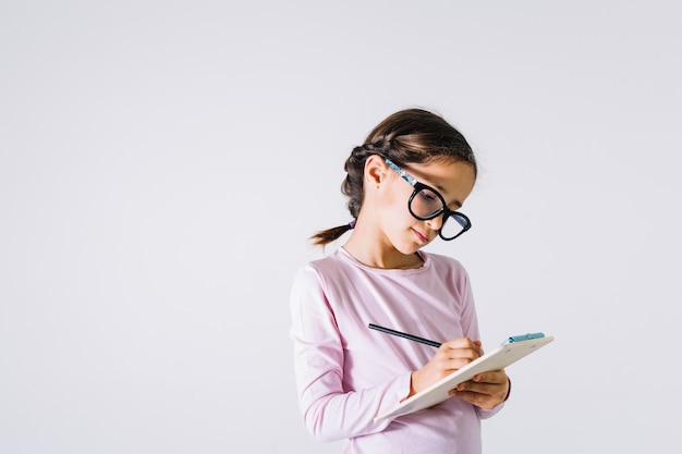 Chica inteligente haciendo notas