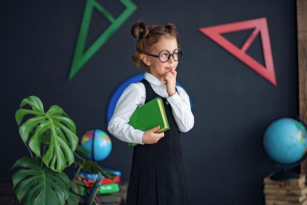 Chica inteligente con libro de texto en la escuela