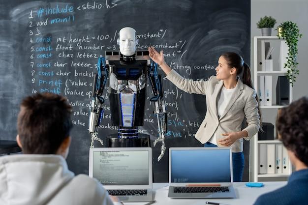 Chica inteligente de pie junto a la pizarra y apuntando al robot mientras hace una presentación de sus características a sus compañeros de clase en el seminario