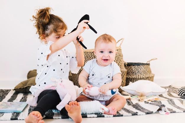 Chica intenta ponerle diadema al bebé