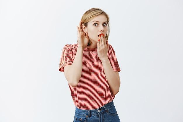 Chica intrigada escuchando a escondidas, jadeando de asombro, escuchando un rumor interesante