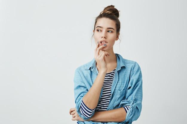 Chica inventando qué hacer a continuación. retrato de mujer pensativa curiosa con peinado de moño, sosteniendo los dedos en los labios mientras mira a un lado y piensa en algo que la molesta