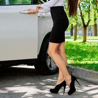 Chica irreconocible abre la puerta de su auto