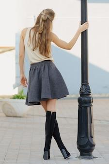 Chica irreconocible con botas y falda corta girando alrededor del poste de la lámpara. disfrutando del sol de otoño.