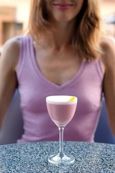 Chica irreconocible detrás de la mesa con un cóctel de brandy de cereza en la terraza al aire libre (foto de enfoque suave)