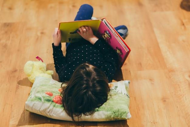 Chica irreconocible leyendo el libro de juguete