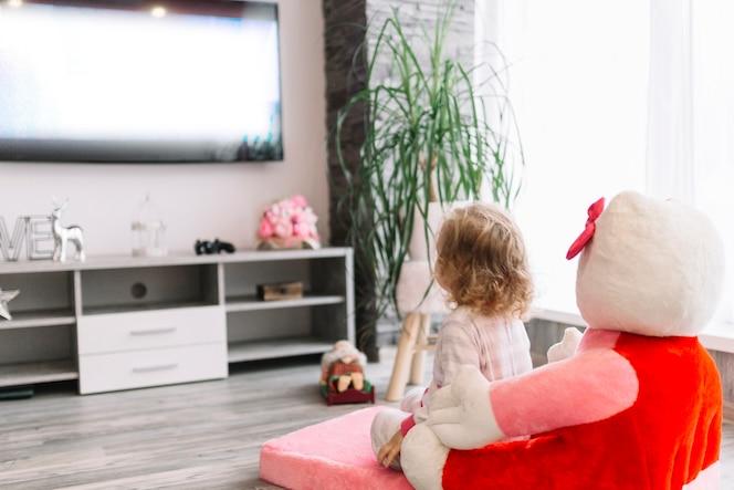 Chica irreconocible viendo televisión