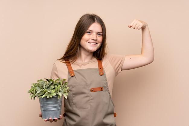 Chica jardinero adolescente sosteniendo una planta celebrando una victoria