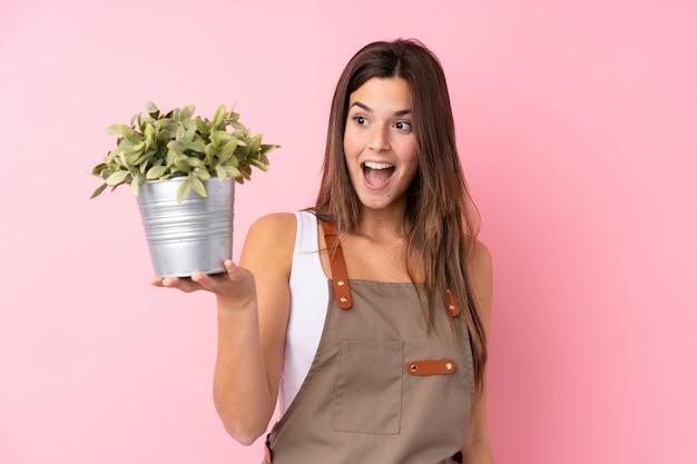 Chica jardinero adolescente sosteniendo una planta con sorpresa y expresión facial conmocionada