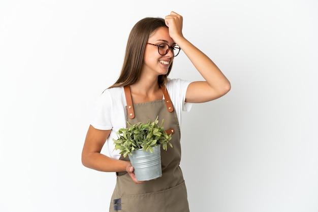 Chica jardinero sosteniendo una planta aislada se ha dado cuenta de algo y tiene la intención de la solución