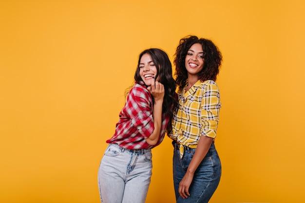Chica en jeans claros se ríe de todo corazón con las bromas de su novia mulata. instantánea en interiores de mujeres de buen humor.