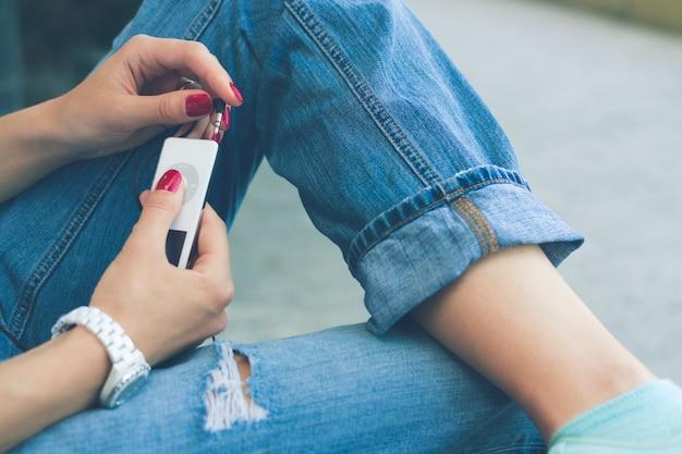 Chica en jeans sentada en el banco y conecta los auriculares a su reproductor de música