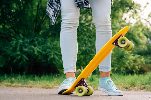 Chica en jeans y zapatillas de deporte de pie en un parque al lado de skate amarillo