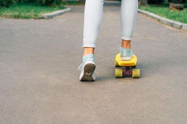 Chica en jeans y zapatillas montando una patineta en el parque