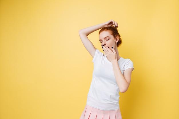 Chica de jengibre cansada cubriendo su boca con los ojos cerrados