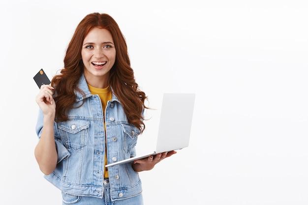 Chica jengibre segura y despreocupada con pecas en chaqueta de mezclilla, que muestra lo fácil que es pagar los productos en línea, sostener una computadora portátil y una tarjeta de crédito negra, sonreír satisfecha, comprar productos, hacer un pedido por internet