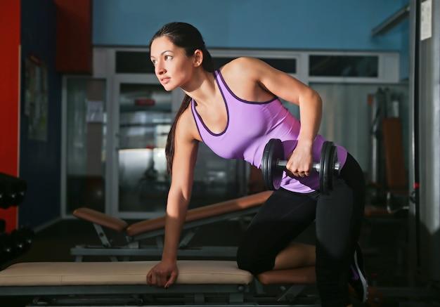 Chica con jinetes en el gimnasio haciendo ejercicios musculares