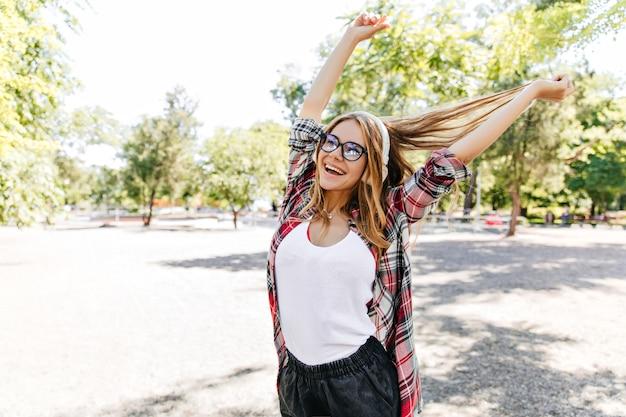 Chica jocund en auriculares expresando felicidad en el parque. señora rubia alegre pasar el fin de semana de verano al aire libre.