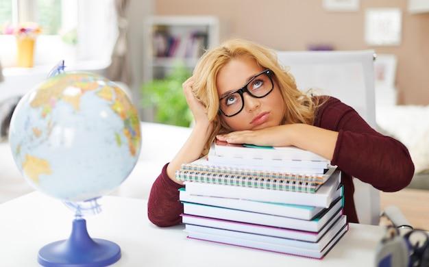 Chica joven aburrida con pila de libros