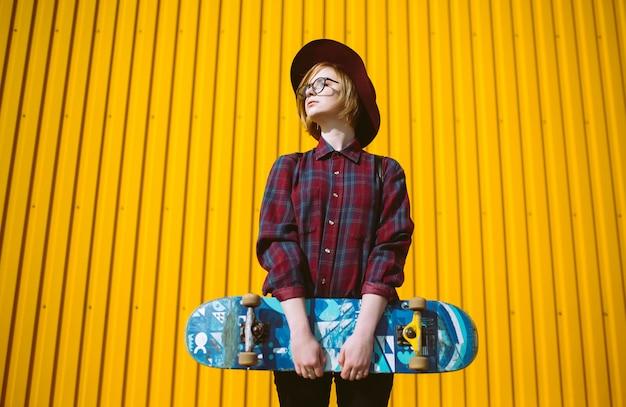 Chica joven adolescente con patín en la mano posando sobre un fondo amarillo. mujer bonita en gafas de sol y sombrero se encuentra en la calle con patín en la mano.