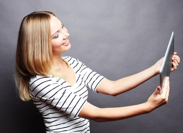 Chica joven adolescente tomando selfie con tableta digital, sobre espacio gris