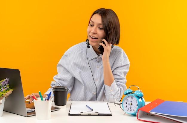 Chica joven alegre del centro de llamadas con auriculares sentados en el escritorio hablando por teléfono y usando la computadora portátil aislado en naranja
