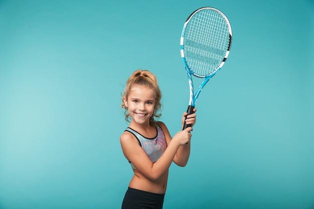 Chica joven alegre deportes jugando tenis aislado sobre pared azul