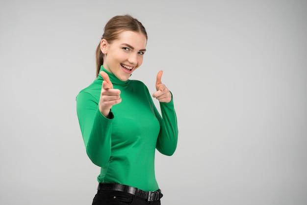 Chica joven alegre feliz que mira la cámara lauthing que señala los fingeres