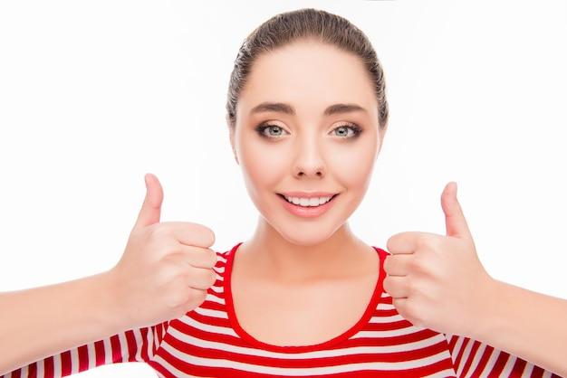 Chica joven alegre mostrando los pulgares hacia arriba y sonriendo