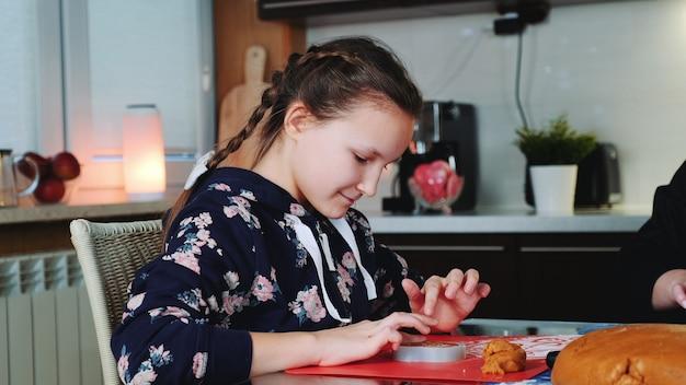 Chica joven alegre que llena el plato de la hornada con masa de pasteles.