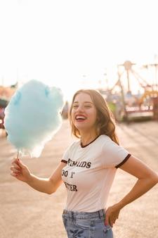 Chica joven con algodón de azúcar en el parque de atracciones