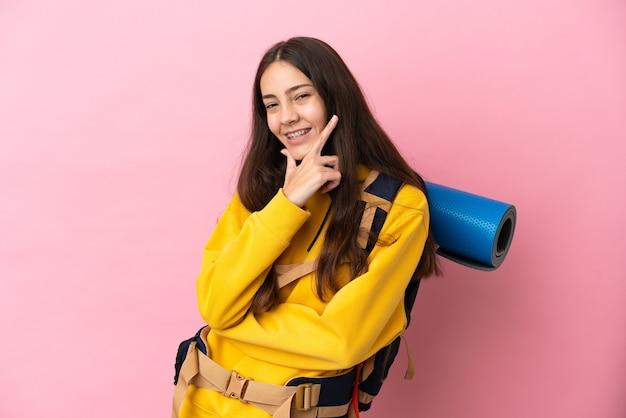 Chica joven alpinista con una mochila grande aislada sobre fondo rosa feliz y sonriente