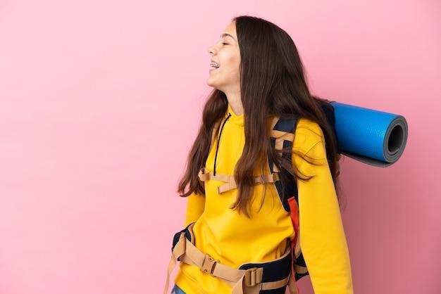 Chica joven alpinista con una mochila grande aislada sobre fondo rosa riendo en posición lateral