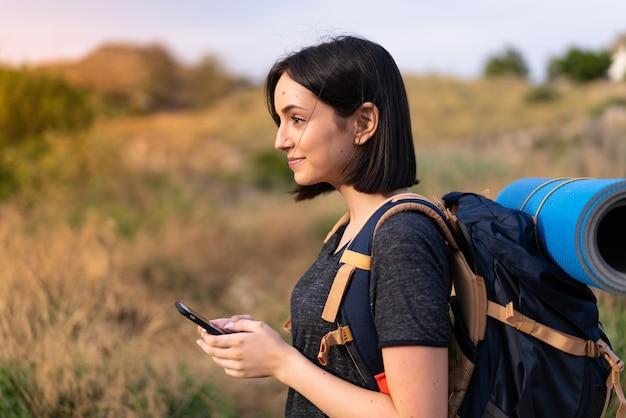 Chica joven alpinista con una mochila grande enviando un mensaje o correo electrónico con el móvil al aire libre