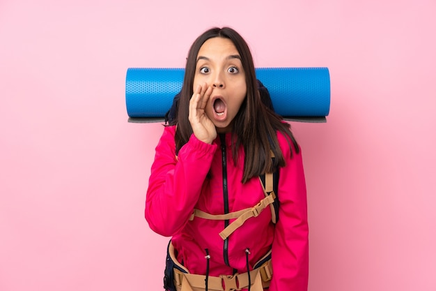 Chica joven alpinista con una mochila grande sobre pared rosa aislada gritando y anunciando algo