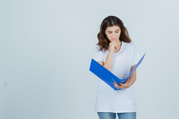 Chica joven apoyando la barbilla en la mano, mirando en la carpeta con camiseta blanca y mirando pensativo. vista frontal.