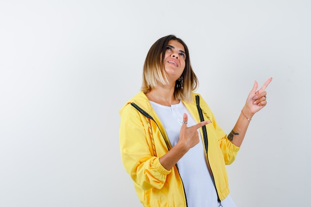 Chica joven apuntando hacia arriba y hacia la derecha con los dedos índices en camiseta blanca, chaqueta amarilla y mirando alegre, vista frontal.