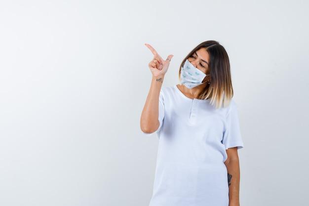 Chica joven apuntando a la izquierda con el dedo índice en camiseta blanca y máscara y mirando confiado, vista frontal.