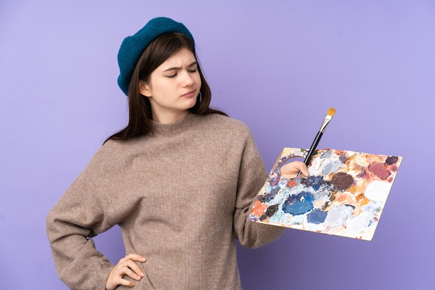 Chica joven artista sosteniendo una paleta sobre pared púrpura con expresión triste