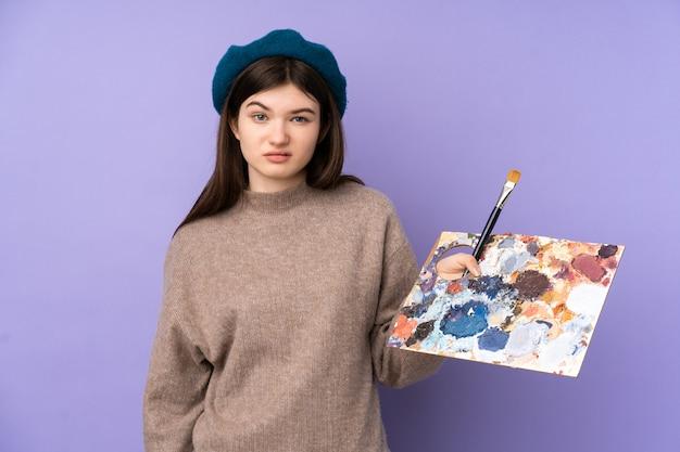 Chica joven artista ucraniana sosteniendo una paleta sobre pared púrpura aislado con expresión triste